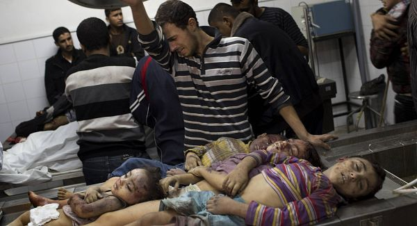 A Palestinian man cries next the dead bodies of four children in the morgue of Shifa Hospital in Gaza City, Sunday, Nov. 18, 2012. An Israeli missile flattened a two-story house in a residential neighborhood of Gaza City on Sunday, killing at least 11 civilians shortly after Israel announced plans to intensify an offensive by attacking the homes of wanted militants, medical officials said. Gaza health official Ashraf al-Kidra says five women, including an 80-year-old woman, and four small children were among the dead. (AP Photo/Bernat Armangue)
